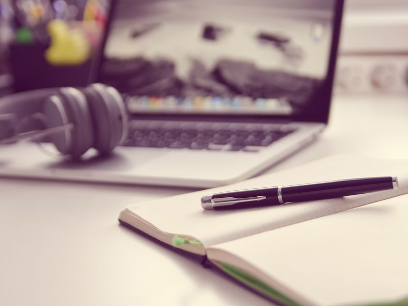 Laptop with earphones and notebook